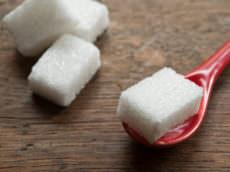 sucre en morceaux et petite cuillère rouge sur fond en bois