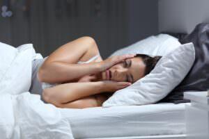 photo d'une femme dans son lit ayant du mal à trouver le sommeil